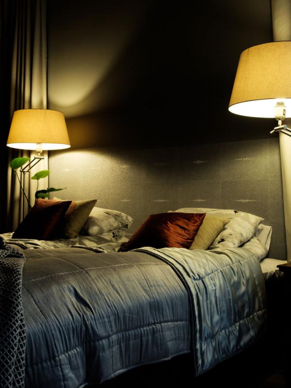 Hotellihenkisen makuuhuoneen keskiössä verho-ja tekstiilisuunnittelu.