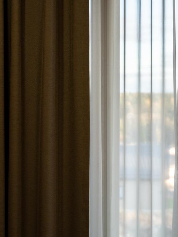 Makuuhuoneen kahdet kontrastiset verhot.